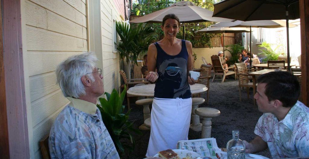 Tina serving in the courtyard with a big smile